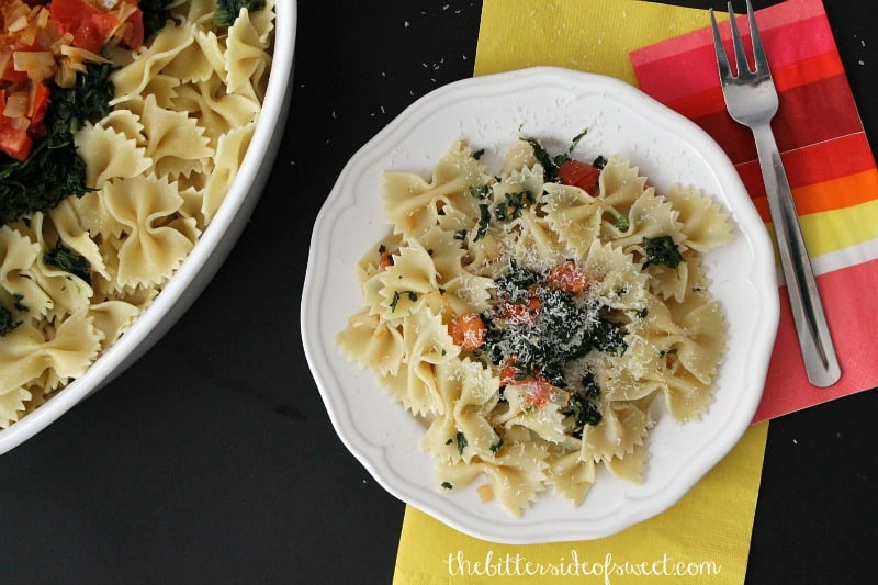 Spinach Tomato Bow Tie Pasta on a white plate with a fork.