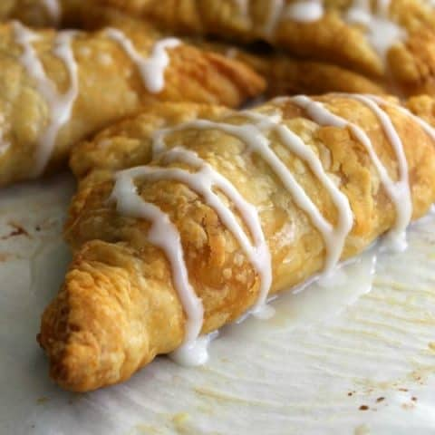 Pumpkin Pie Turnovers on parchment paper with icing drizzled over the top