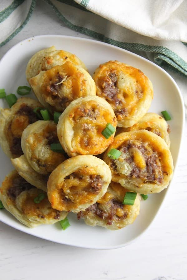 Puff Pastry Sausage Cheddar Pinwheels on white plate