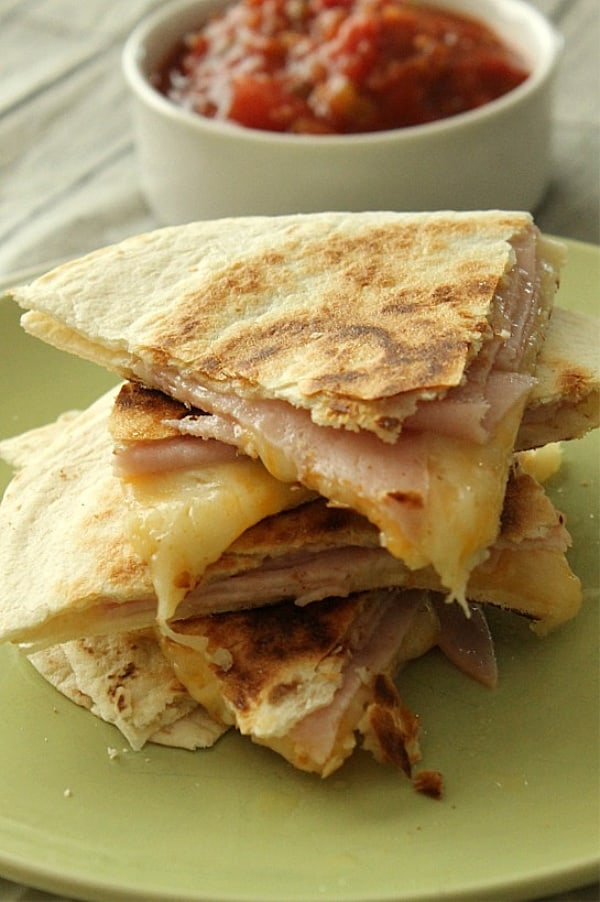 Ham and Cheese Quesadillas on stacked on green plate