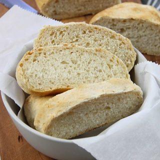 Homemade Italian Bread in gray bowl on brown cutting board