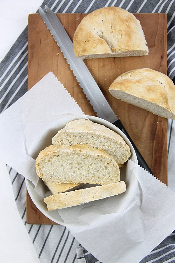 Homemade Italian Bread on cutting board with knife and bowl