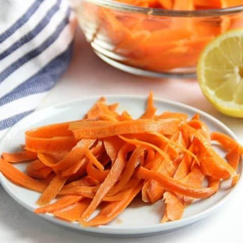 Lemon Carrot Salad on white plate with lemon