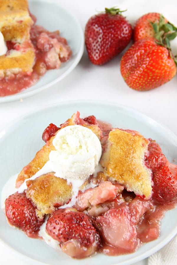 Strawberry Cobbler on white plate with ice cream on top