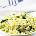 Cheesy Spinach Orzo on white plate with blue and white napkin in the background