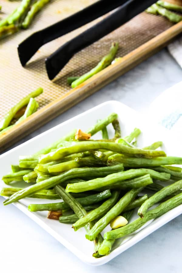 Sheet Pan Roasted Green Beans on white plate with sheet pan in background