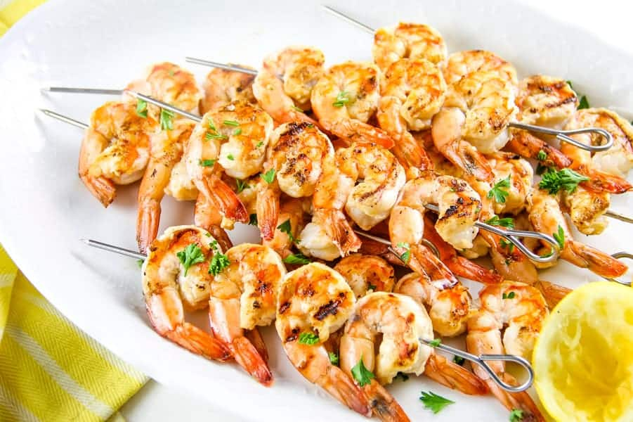 Grilled Lemon Shrimp Skewers on white plate with yellow towel topped with parsley