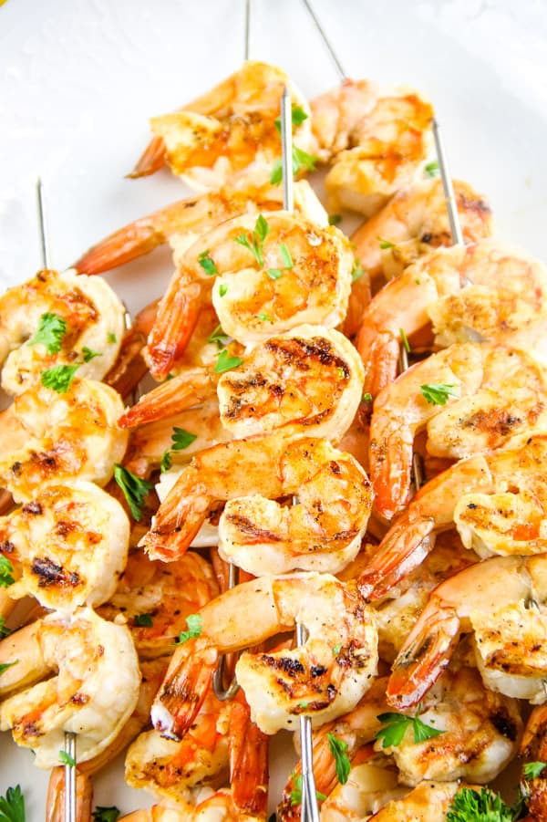 Grilled Lemon Shrimp Skewers on metal skewers stacked on white plate