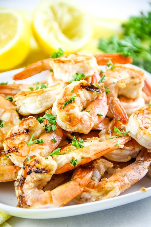 Grilled Lemon Shrimp Skewers with shrimp stacked on a white plate