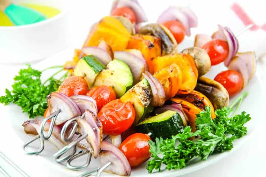 Grilled Vegetable Skewers on white plate with parsley and bowl of olive oil in background