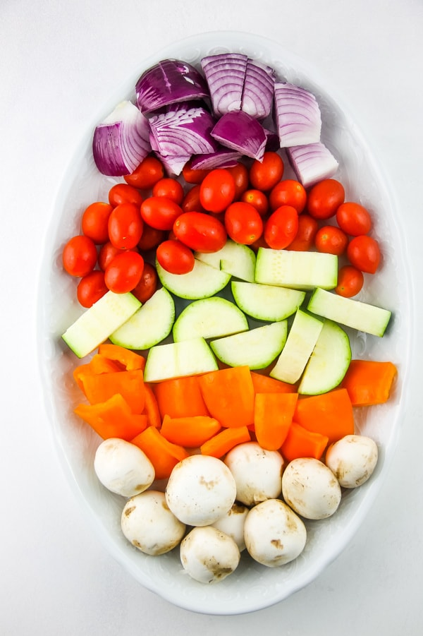 Grilled Vegetable Skewers with raw vegetables on white plate