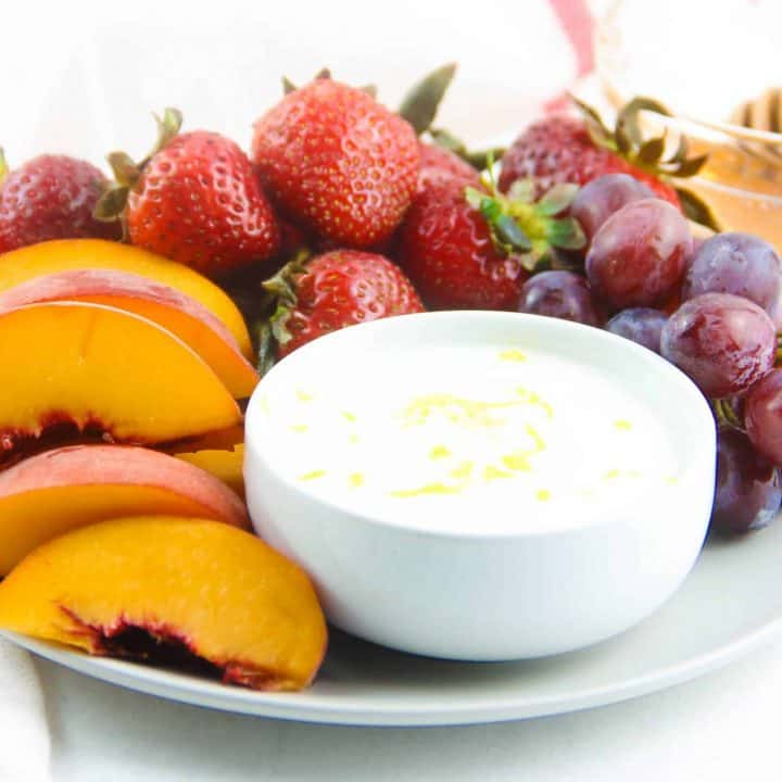 Honey Yogurt Dip in white bowl on grey plate with fresh fruit.