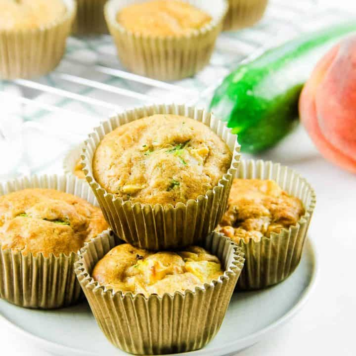 Peach Zucchini Oatmeal Muffins on white plate with zucchini and peach in background.