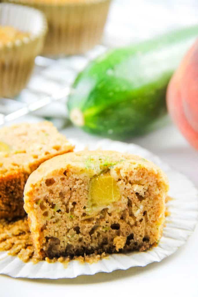 Peach Zucchini Oatmeal Muffins cut in half on liner