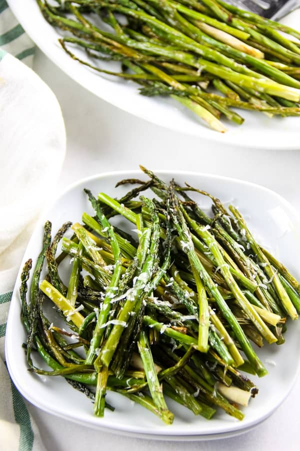 Sheet Pan Roasted Asparagus on small white plate cut into small pieces