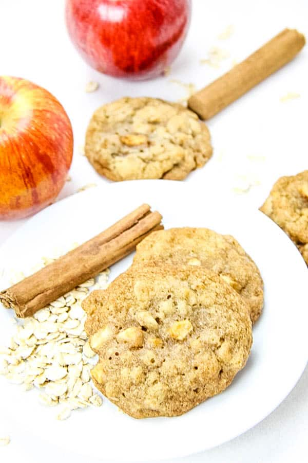 Apple Cinnamon Oatmeal Cookies on white plate with cinnamon sticks and oats