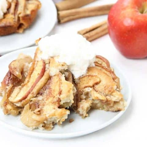 Easy Apple Cobbler on white plate with ice cream on top.
