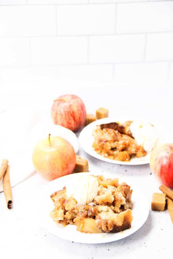 Caramel Apple Cobbler on white plates surrounded by fresh apples, caramel and cinnamon sticks
