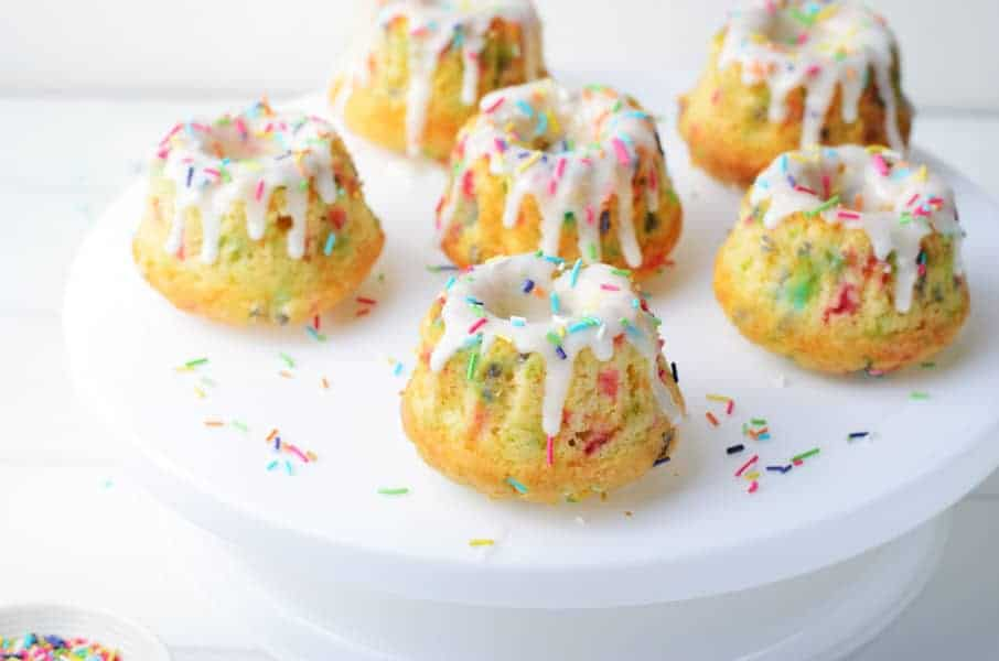 Funfetti Mini Bundt Cakes with 6 cakes on white cake plate