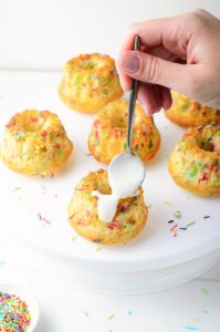 Funfetti Mini Bundt Cakes with spoon drizzling glaze