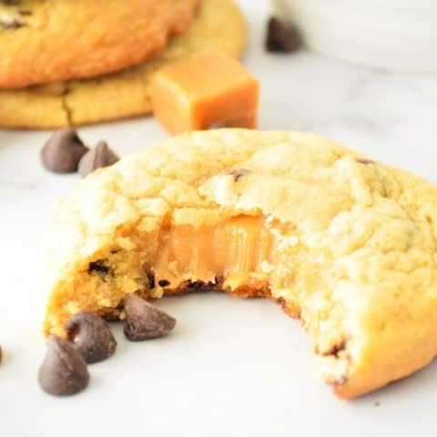 Chocolate Chip Caramel Cookies with bite and caramel oozing out