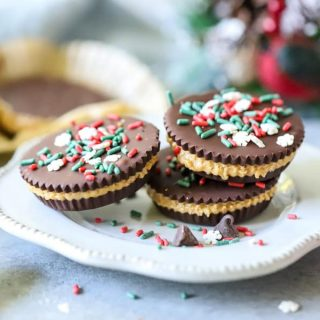Homemade Peanut Butter Cups stacked on white plate with holiday sprinkles