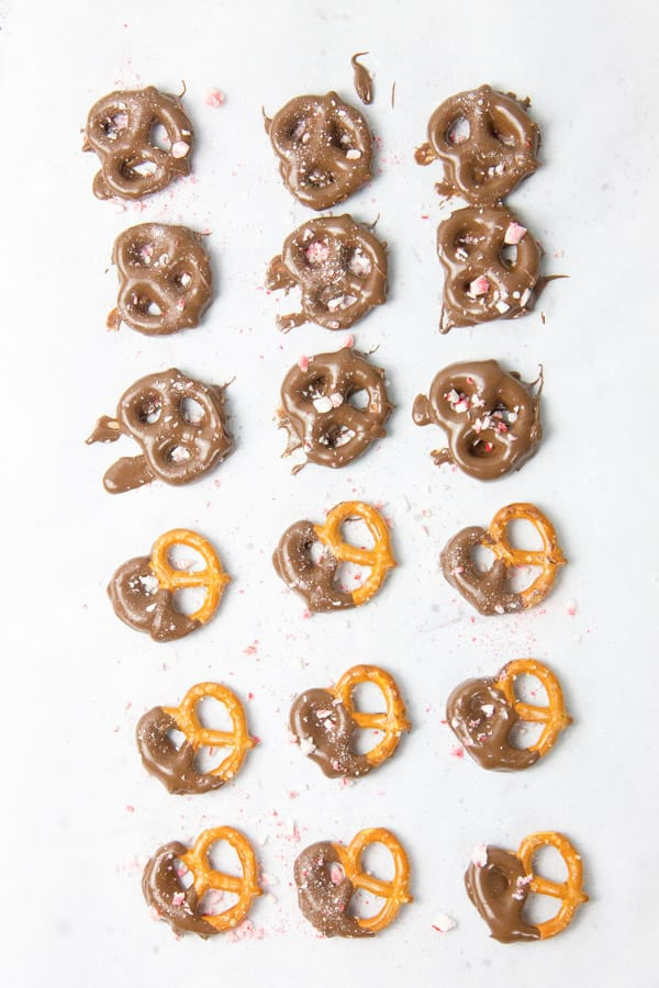 Pretzels covered in chocolate laid out on parchment paper
