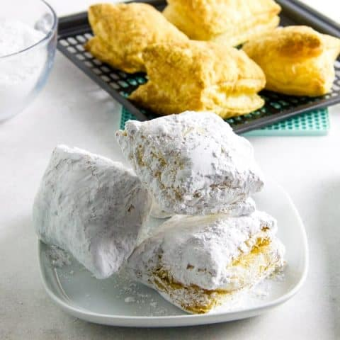 Air Fryer Beignets with tongs and bowl of powdered sugar.