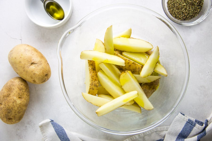 potatoes in bowl with olive oil.