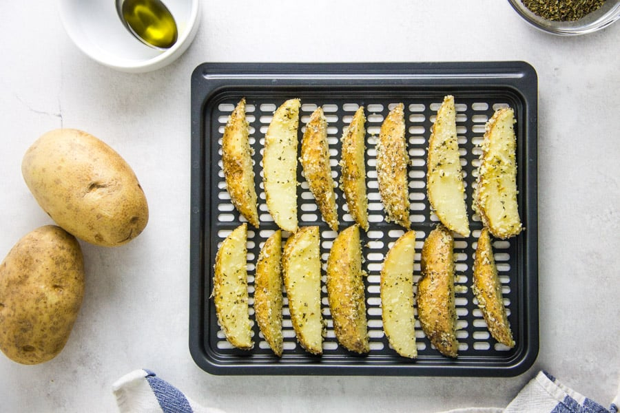 Air Fryer Parmesan Potato Wedges on crisper tray uncooked.