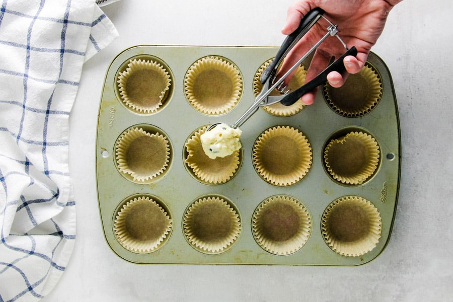 putting scoop of muffin mix into muffin pan