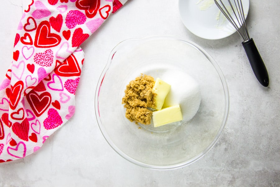 uncooked cookie ingredients in glass bowl with butter and sugar