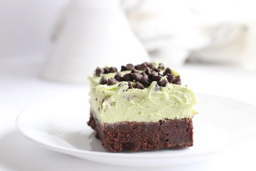 Mint Chocolate Chip Brownies slice on white plate with frosting on top.