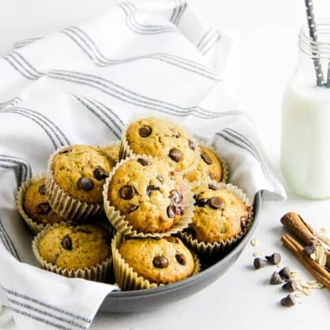 Muffins in bowl with glass of milk.
