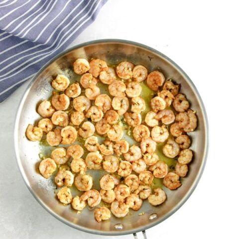 uncooked shrimp in glass bowl cooked in pan.