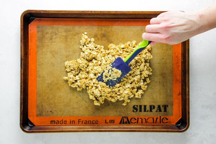spreading out granola on sheet pan.