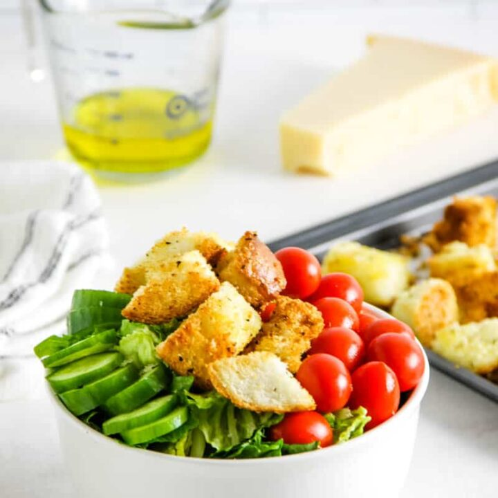 croutons topped on salad in white bowl.