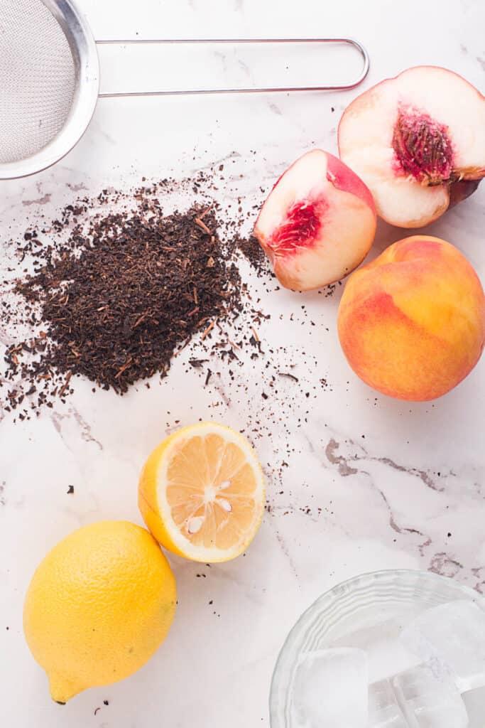 Ingredients for Peach Black Tea Lemonade on white background.