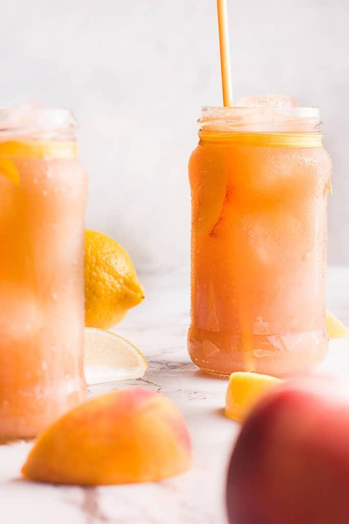 Peach Black Tea Lemonade in glass jars with straw.