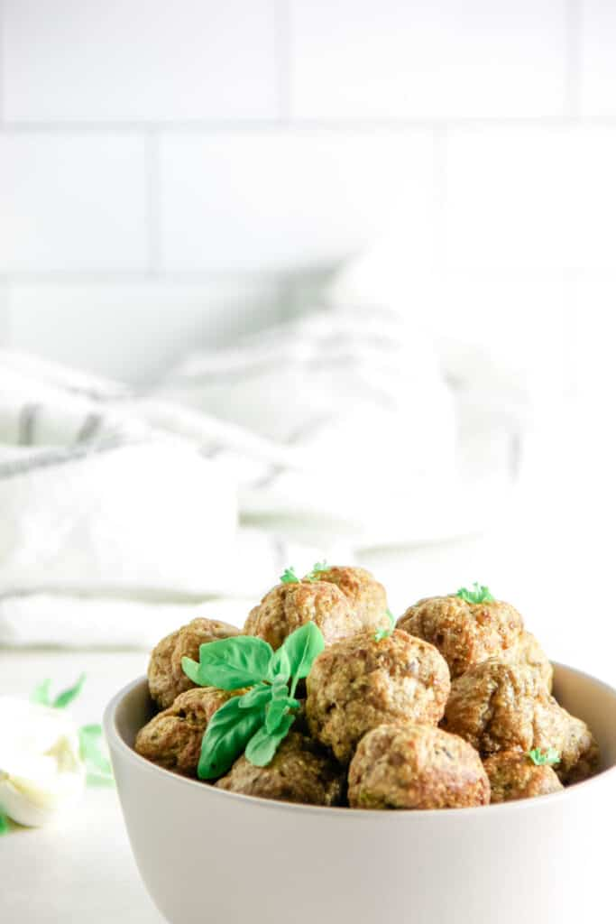 Air Fryer Turkey Meatballs in white bowl with fresh basil.