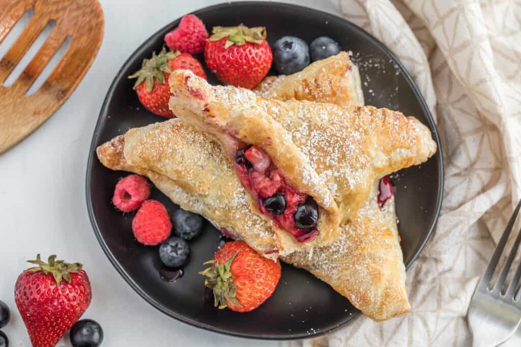 mixed berry turnover cut in half on plate.