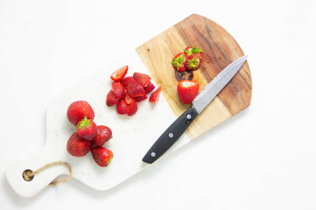 cut up strawberries on cutting board.