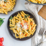 Creamy Tomato Spinach Pasta topped with cheese.
